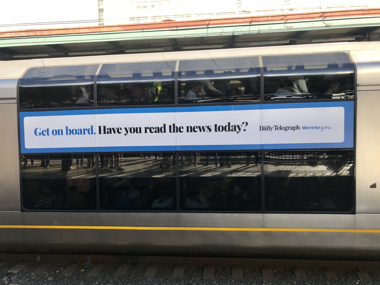"Photo of subway-type train with NewsCorp Australia wrap ad. Text reads, ""Get on board. Have you read the news today?"""