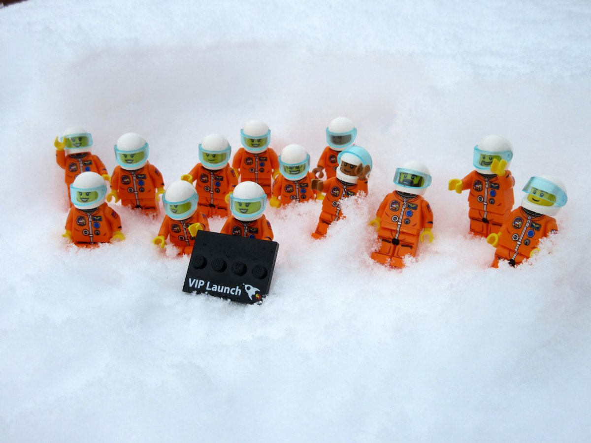 Thirteen orange lego people nestled in the snow holding a black sign that reads 'VIP Launch'