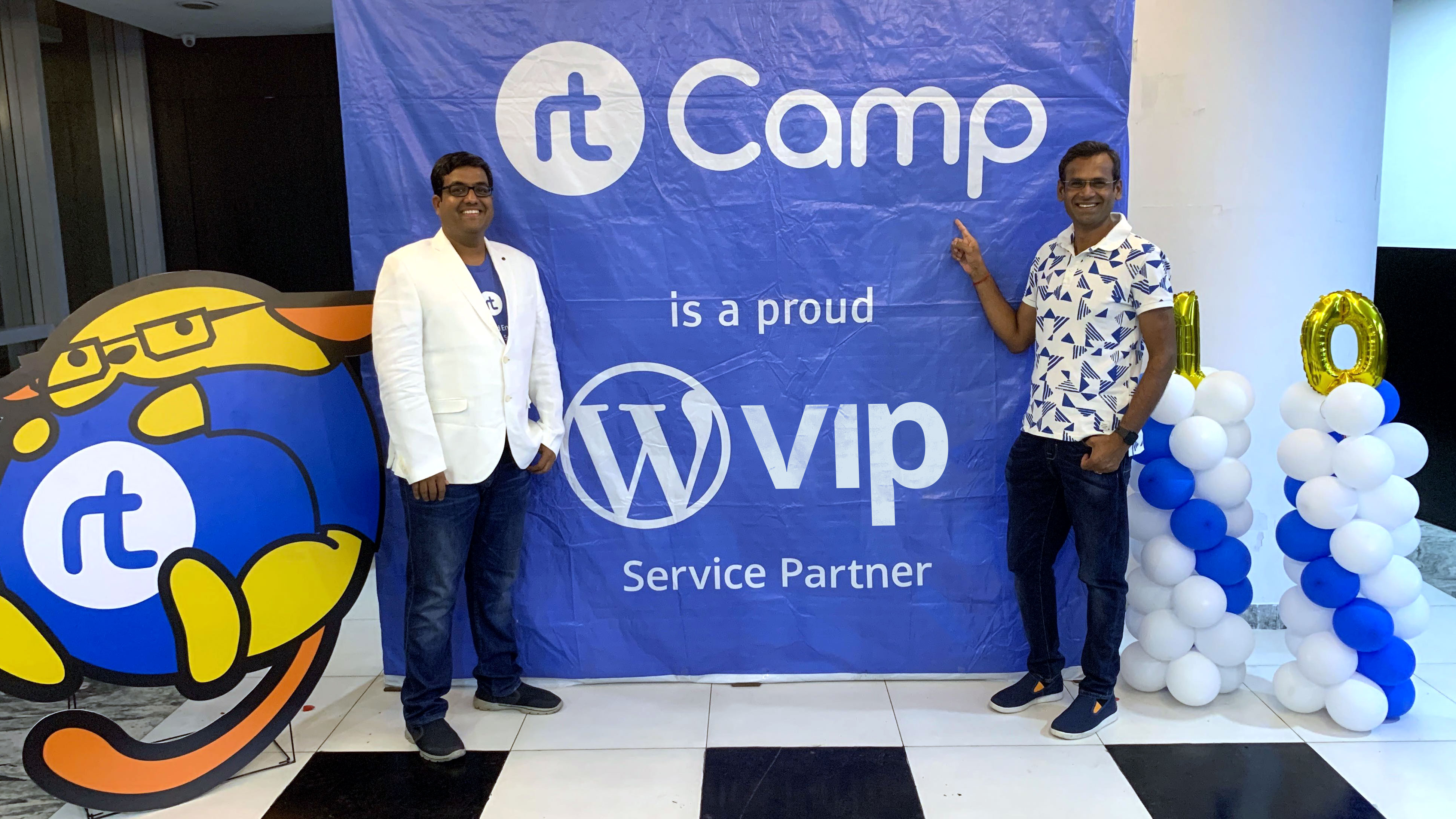 At WordCamp Kolkata, CEO of rtCamp Rahul Bansal wears a white blazer and poses next to VIP Anand Natarajan in front of a blue banner celebrating rtCamp as a featured partner of WordPress VIP